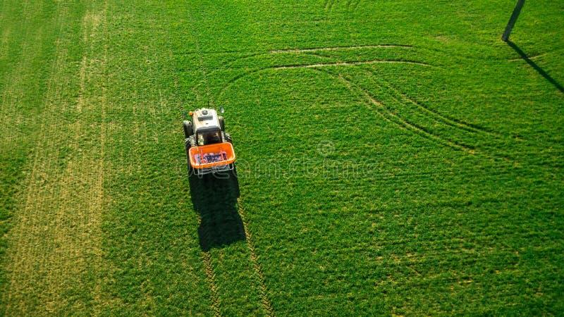 Le tracteur fait l'engrais sur le champ Levé aérien photographie stock libre de droits
