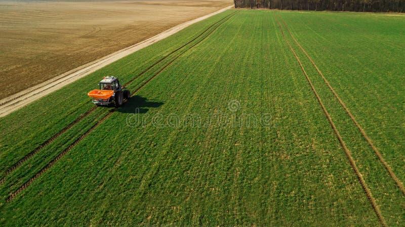 Le tracteur fait l'engrais sur le champ Levé aérien photographie stock