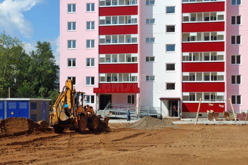 Le tracteur fonctionne près du bâtiment sur le chantier de construction à l'été s photo stock