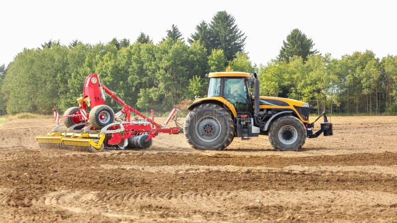 Le tracteur jaune tire le mécanisme de ensemencement rouge au-dessus du champ sec, arbres à l'arrière-plan photographie stock
