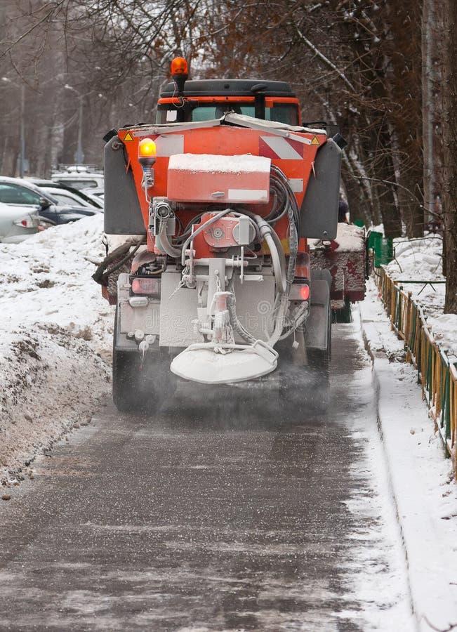 Le tracteur jette le réactif solide sur le trottoir pour fondre la neige Rues de nettoyage de Moscou en hiver photos stock