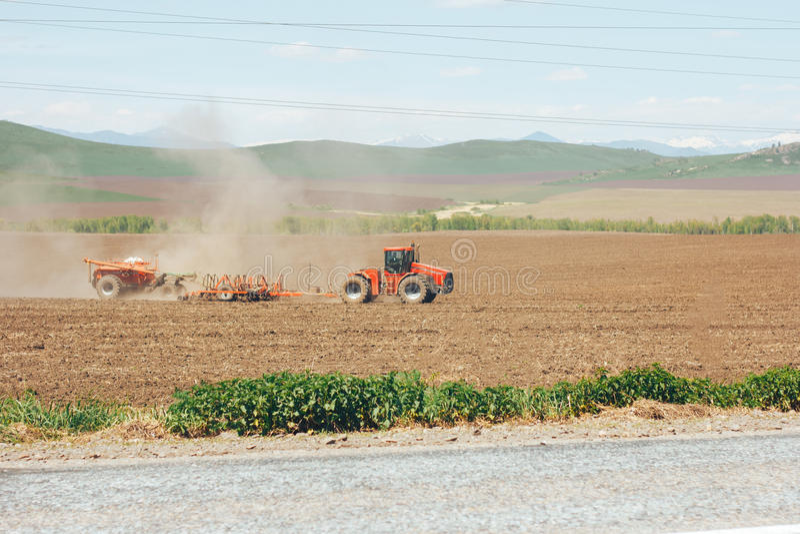 Le tracteur laboure la terre photos stock