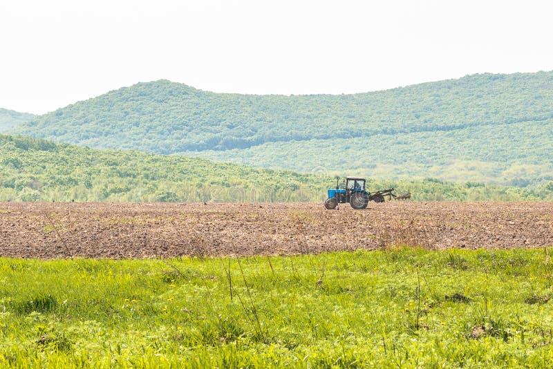Le tracteur laboure le sol avec les mottes de terre formidables d'un cultivateur les lits et en pr?parant le champ pour l'encemen photos stock