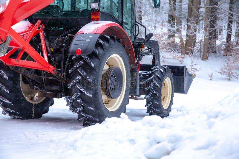 le tracteur nettoie la route de la neige pendant l'hiver photographie stock libre de droits