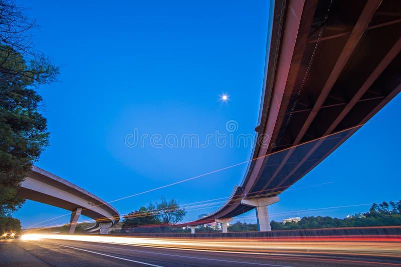 Le trafic de nuit avec la lumière traîne sur l'échange de route photos libres de droits