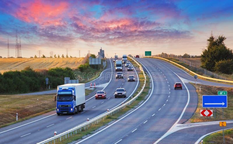 Le trafic de route dans le coucher du soleil avec des voitures et des camions photos libres de droits