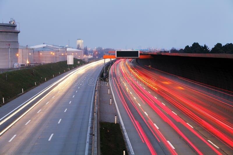 Le trafic de vitesse au temps dramatique de crépuscule - la lumière traîne sur le motorwa image stock
