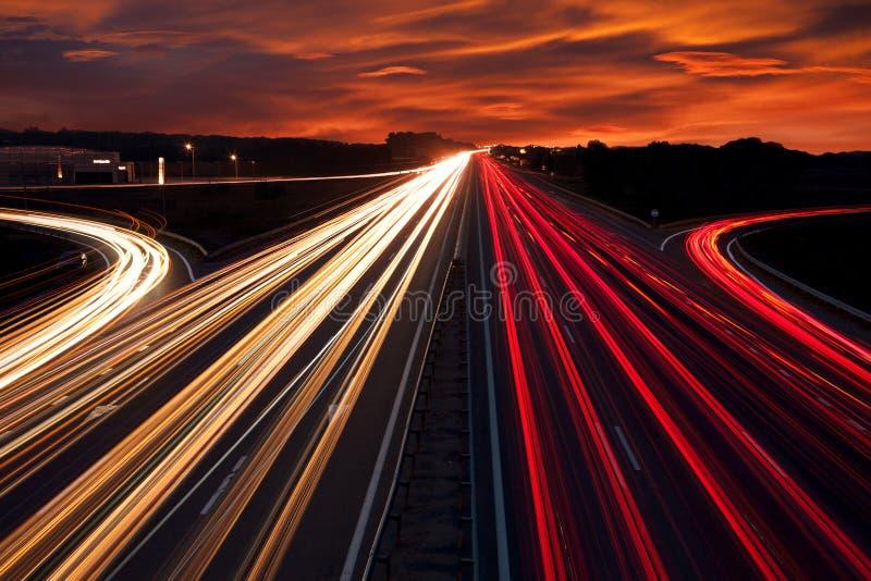 Le trafic de vitesse - la lumière traîne sur la route d'autoroute la nuit image libre de droits