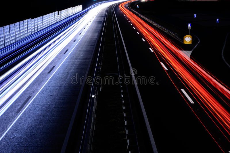 Le trafic de vitesse - la lumière traîne sur la route d'autoroute la nuit, longtemps photo stock