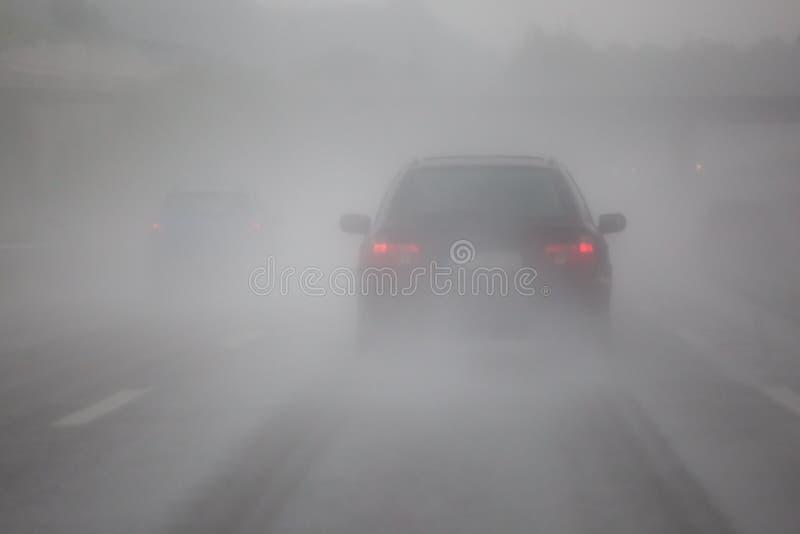 Le trafic de voiture avec le brouillard et la pluie image stock