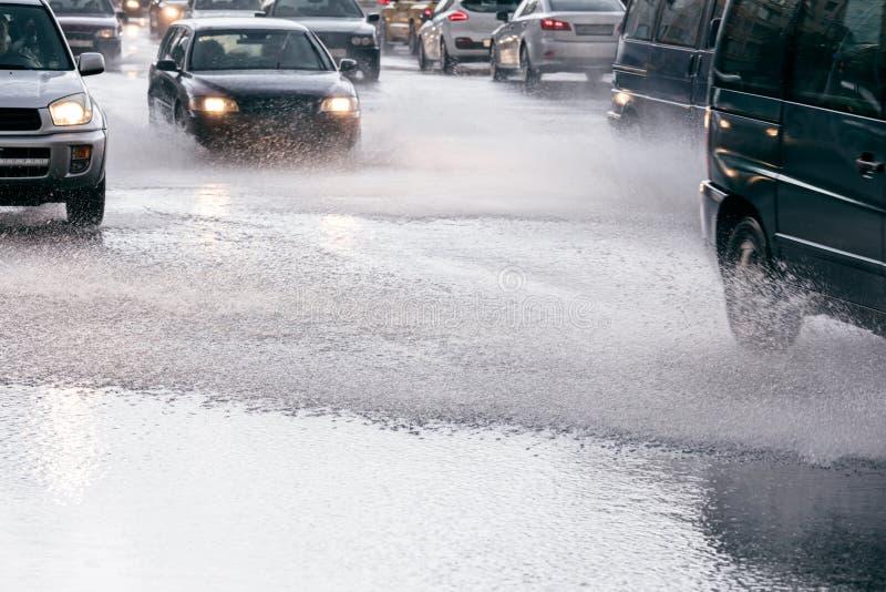 Le trafic de voiture conduisant sur la route urbaine inondée pendant des heures de pointe en Ra image libre de droits