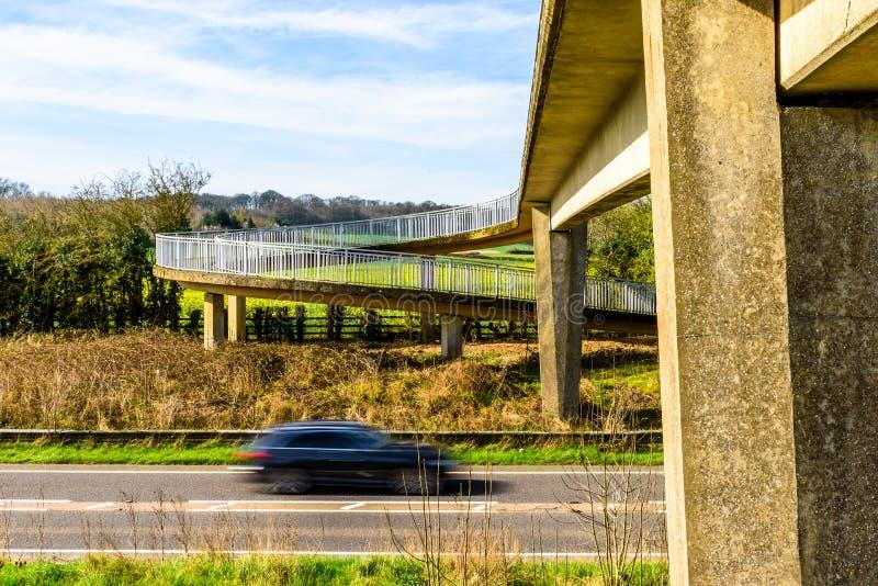 Le trafic de voiture occupé sous le pont piétonnier au-dessus de l'autoroute britannique image libre de droits