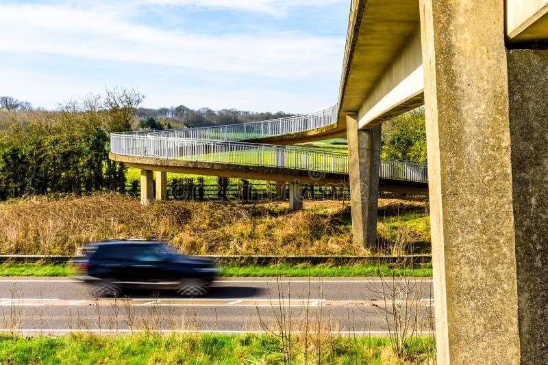 Le trafic de voiture occupé sous le pont piétonnier au-dessus de l'autoroute britannique image stock