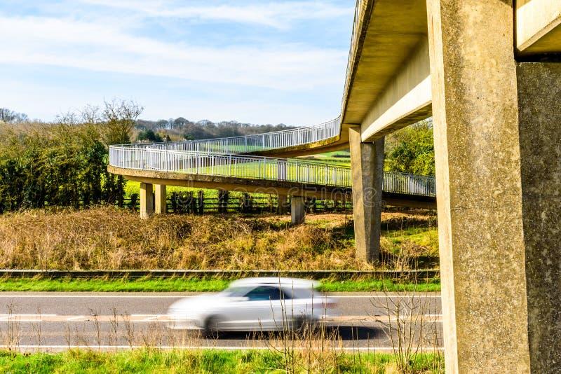 Le trafic de voiture occupé sous le pont piétonnier au-dessus de l'autoroute britannique photo libre de droits