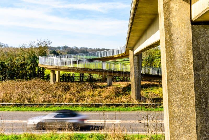 Le trafic de voiture occupé sous le pont piétonnier au-dessus de l'autoroute britannique photo stock