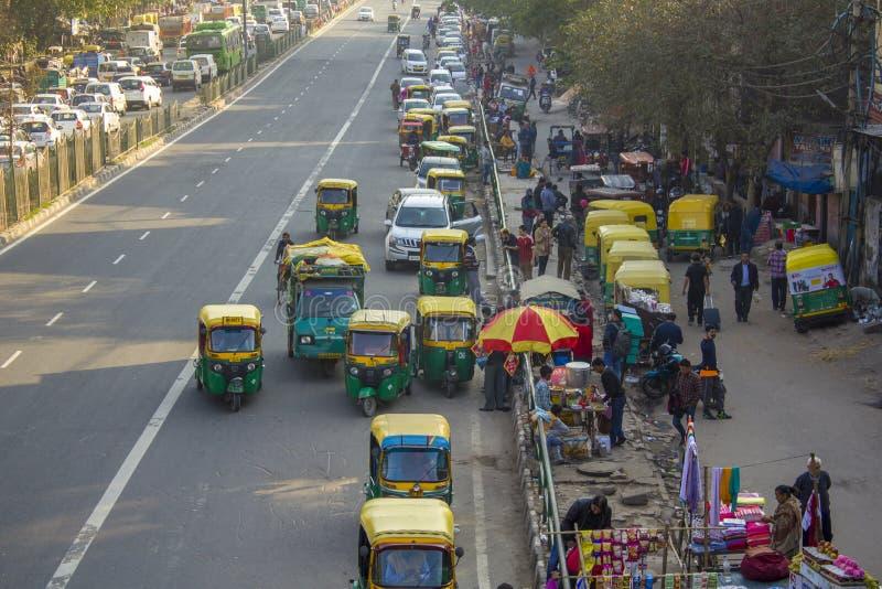 Le trafic urbain indien et les pousse-pousse jaunes verts roulent au sol le stationnement près des piétons et de la vente ambulan image stock