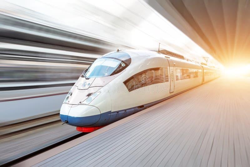 Le train à grande vitesse moderne se déplace rapidement le long de la plate-forme photographie stock