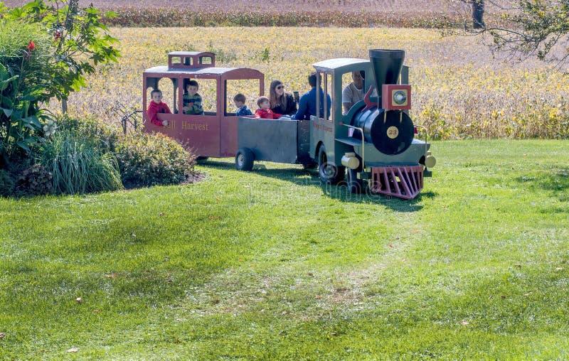 Le train conduit les visiteurs avec plaisir par une ferme de potiron photographie stock