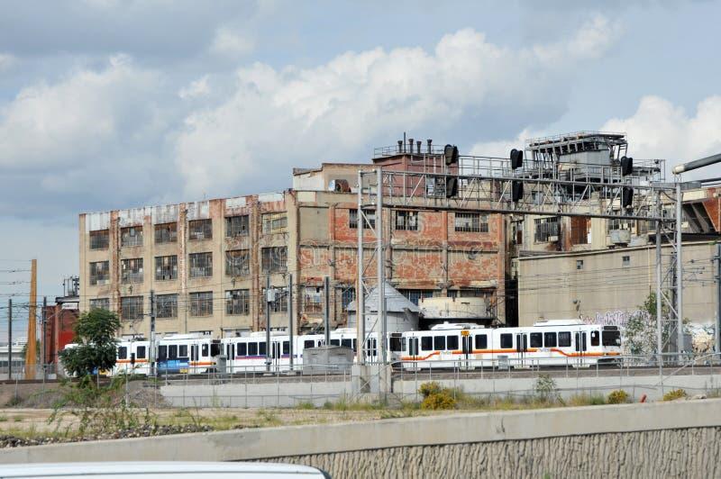 Le train de rail de lumière de RDT passe à de vieilles portes l'usine en caoutchouc image stock