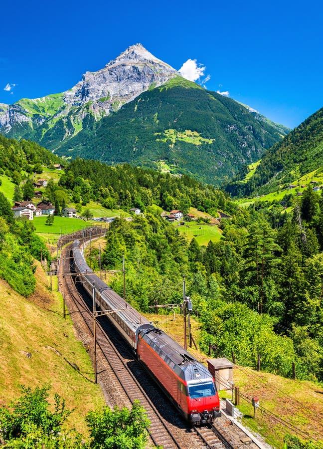 Le train interurbain monte le chemin de fer de Gotthard - Suisse photographie stock libre de droits