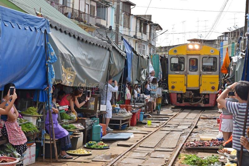 Le train jaune est arrivé tandis que les gens prennent des photos et des vidéos au marché de chemin de fer de Maeklong image stock