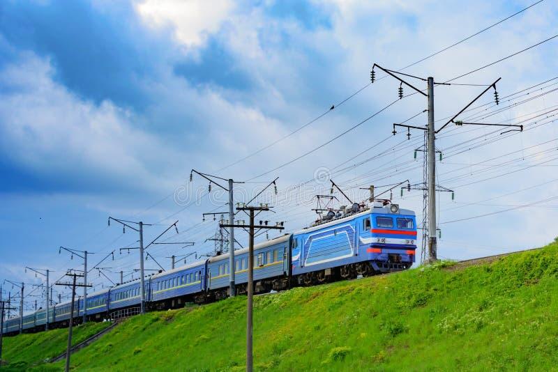 Le train voyage à une réunion de la zone avec les nuages gris photographie stock