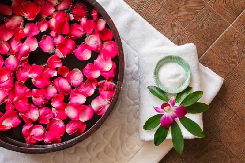 Le traitement de pédicurie de station thermale avec le bain de pied dans la cuvette, pétales de rose rouges, orchidée, pied frott photographie stock libre de droits