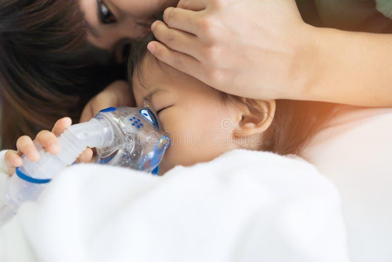 Le traitement de respiration de bébé asiatique avec la mère font attention, au RO photos stock