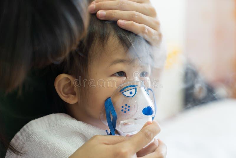 Le traitement de respiration de bébé asiatique avec la mère font attention, au RO image stock