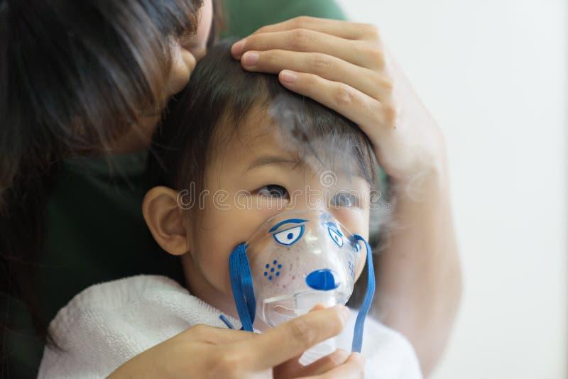 Le traitement de respiration de bébé asiatique avec la mère font attention, au RO photographie stock libre de droits