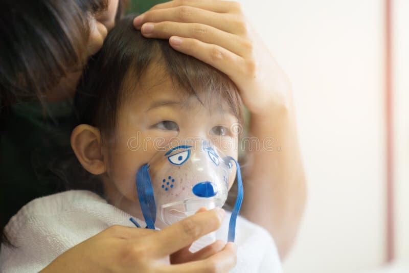 Le traitement de respiration de bébé asiatique avec la mère font attention, au RO images stock