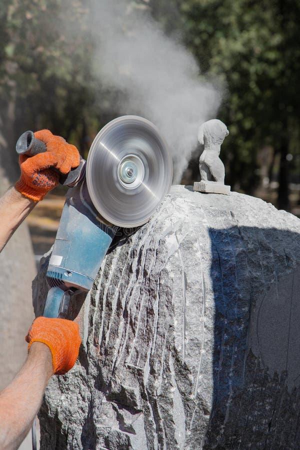 Le traitement du granit en pierre sauvage de gabbro avec une broyeur d'angle, le sculpteur crée un chef d'oeuvre photographie stock
