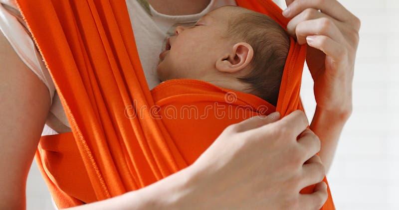 Le transport de femme nouveau-né dans le bébé s'accrochent images libres de droits