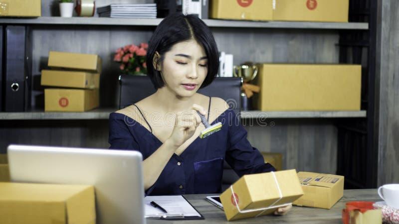 Le travail de d?marrage ? l'entrepreneur de lieu de travail pr?pare pour livrer emball? dans le carton pour livrer les clients, c photo stock