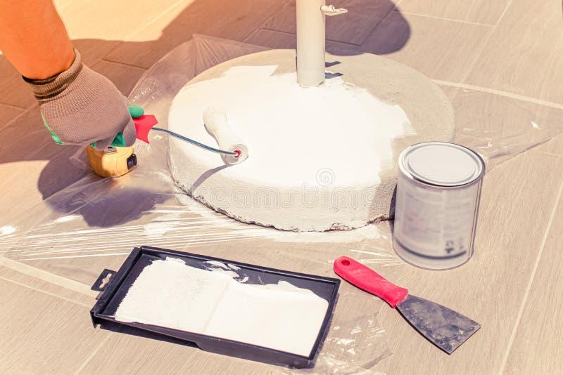 Le travail de nettoyage et de peinture de la base de parapluie de soleil Concept des travaux de réparation et de rénovation à éch images stock