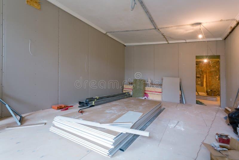 Le travail de processus d'installer des cadres en métal pour la cloison sèche de plaque de plâtre pour des murs de gypse en appar images libres de droits