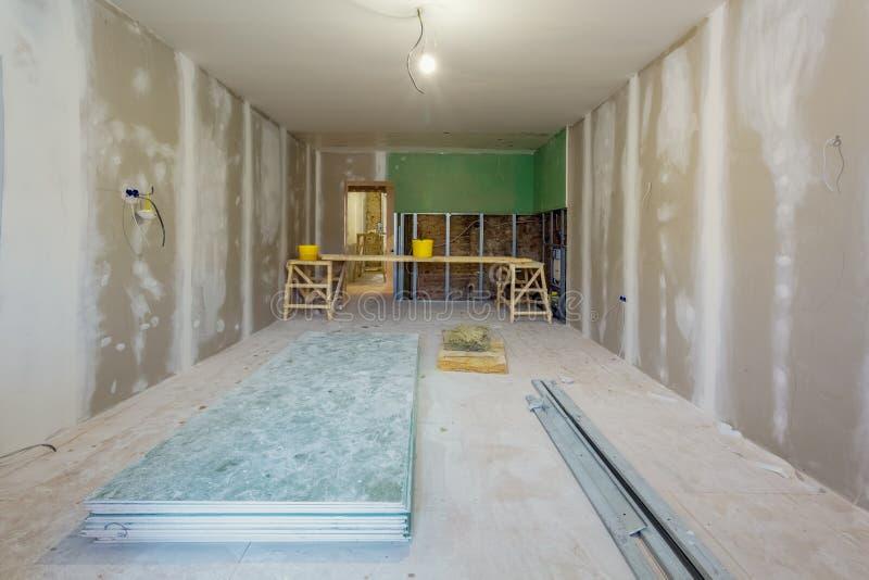 Le travail de processus d'installer les cadres en métal et la cloison sèche de plaque de plâtre pour des murs de gypse en apparte image stock