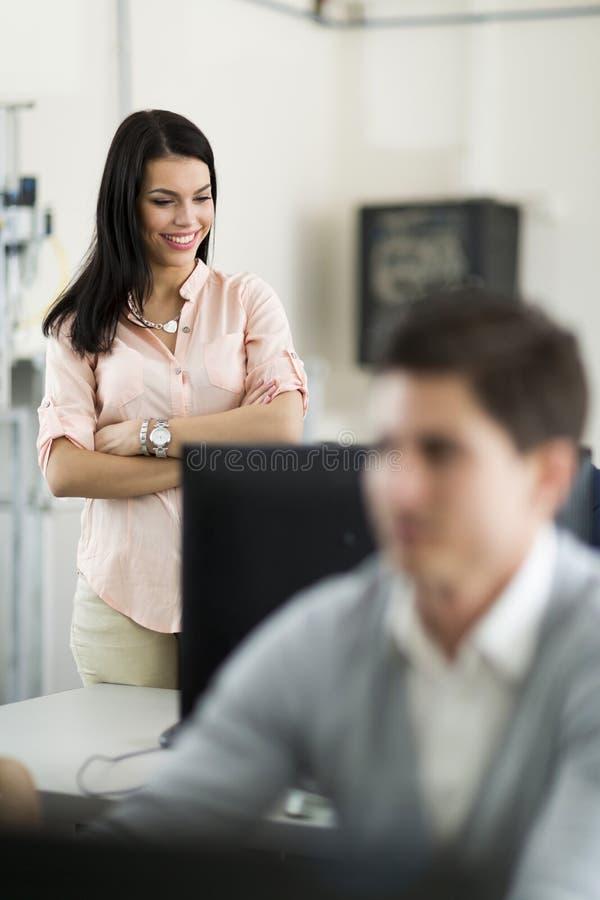 Le travail des beaux jeunes étudiants de surveillance de professeur féminin dans un Cl image stock