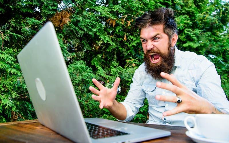 Le travail ? distance i Hippie occup? avec ind?pendant Wifi et ordinateur portable Internet lent irritant photo stock