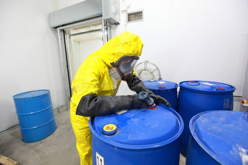 Le travail risqué - le professionnel dans le remplissage uniform barrels avec des produits chimiques photos stock