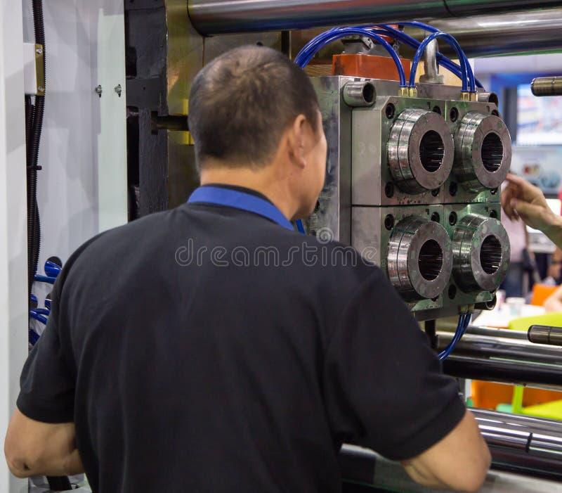Le travailleur actionnent la machine de presse de moulage par injection image libre de droits