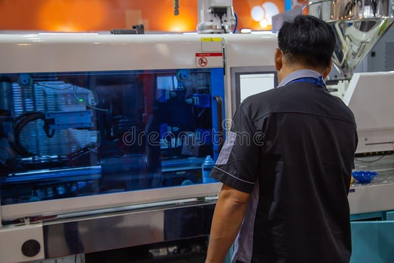 Le travailleur actionnent la machine en plastique de presse de moulage par injection images stock