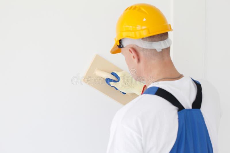 Le travailleur aligne avec le papier sablé photo libre de droits