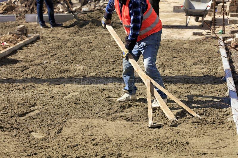 Le travailleur aligne la base avec un niveau en bois pour étendre des tuiles sur le trottoir contre le chantier de construction photo libre de droits