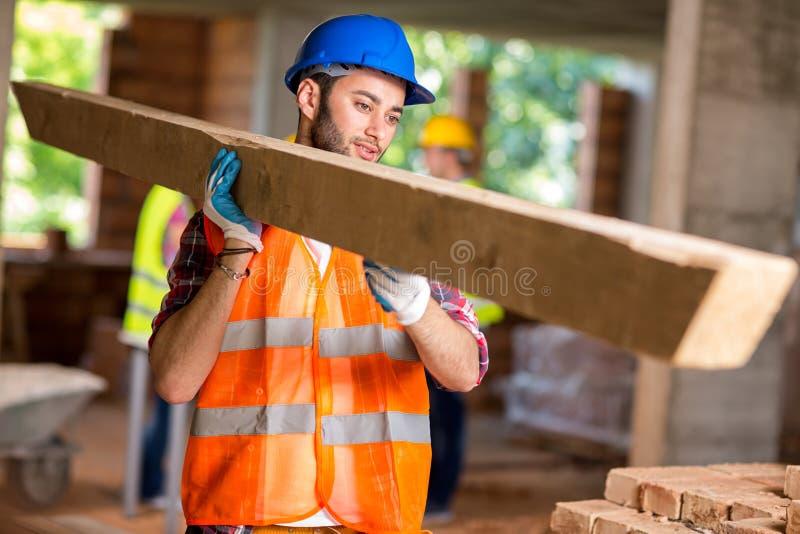 Le travailleur apportent le bois de construction de construction photo stock