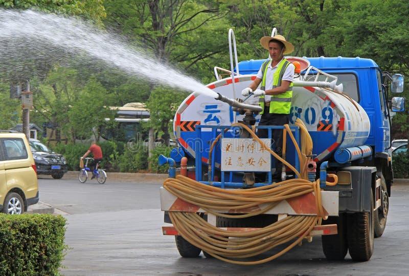 Le travailleur arrose la rue au jet dans Lijiang, Chine images stock