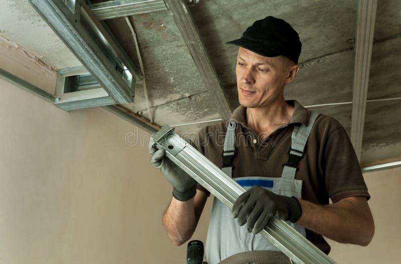 Le travailleur assemble le cadre en métal de profil photos stock