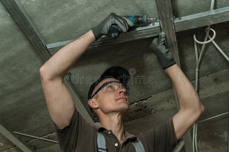 Le travailleur assemble le cadre en métal de profil images libres de droits