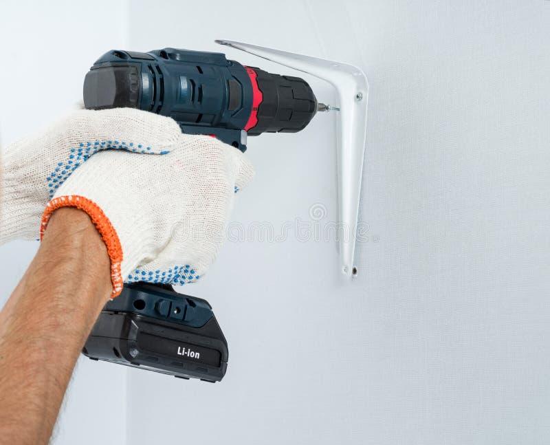 Le travailleur attache la parenthèse au mur avec un tournevis sans fil photo stock