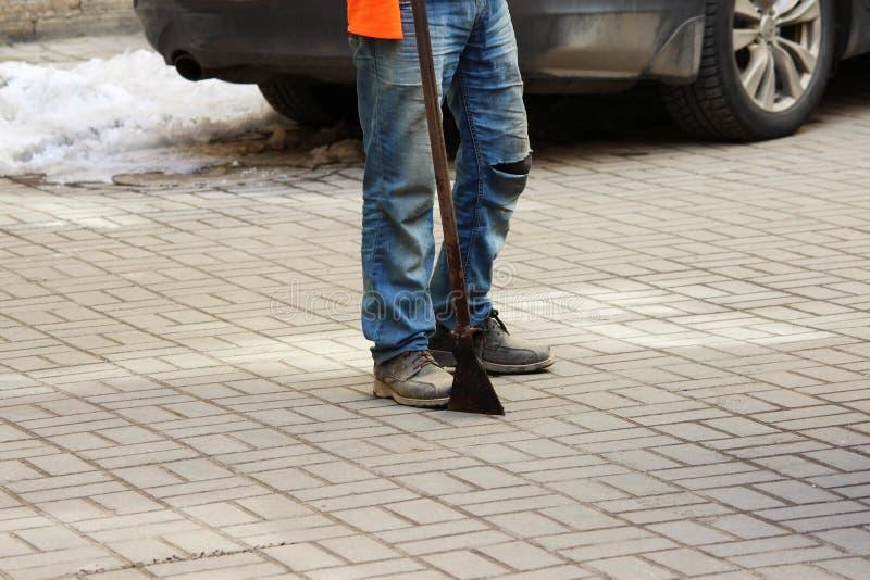 Le travailleur avec un pic à glace dans des ses mains dégage la cour intérieure entre les maisons de la saleté, la neige et la gl photo libre de droits